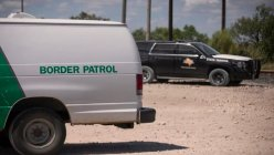 A Texas prosecutor reduces charges after migrants claim they were marched to private land and then held for trespassing.